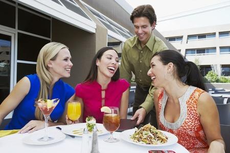 enjoyable: Waiter Bringing Check to Women in Restaurant