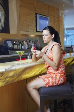 Woman Text Messaging at a Bar Stock Photo - 12737017