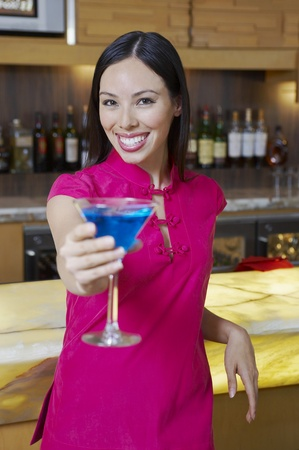 Woman Holding out a Blue Martini Stock Photo - 12737019