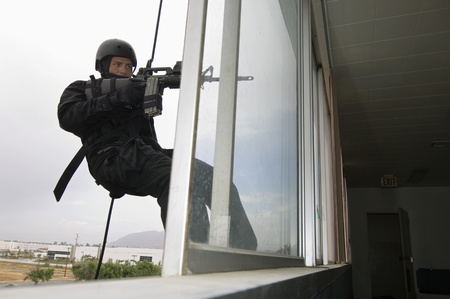 SWAT Team Officer Rappelling and Aiming Gun Stock Photo - 12737059