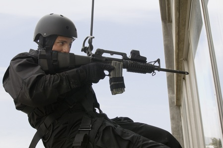 rappeller: SWAT Team Officer Rappelling and Aiming Gun