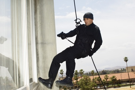 abseiling: SWAT Team Officer Rappelling and Aiming Gun