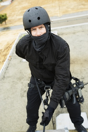 SWAT Team Officer Rappelling from Building Stock Photo - 12737064