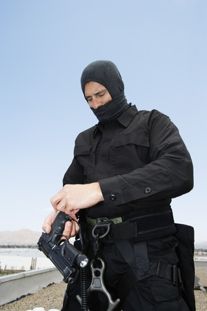 SWAT Team Officer Loading Pistol Stock Photo - 12737071