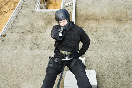 abseil: SWAT Team Officer Rappelling and Aiming Gun