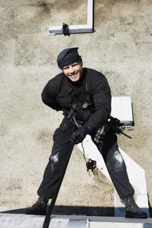 SWAT Team Officer Rappelling from Building Stock Photo - 12737075