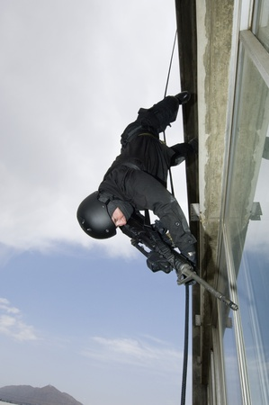 SWAT Team Officer Rappelling from Building Stock Photo - 12737079