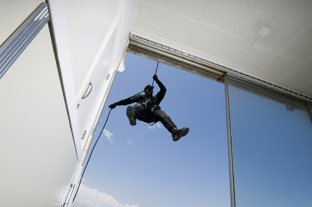 SWAT Team Officer Rappelling from Building Stock Photo - 12737081