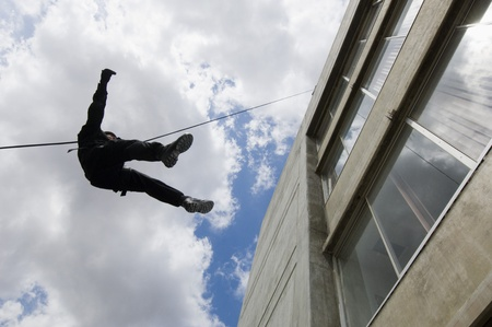 SWAT Team Officer Rappelling from Building Stock Photo - 12735684