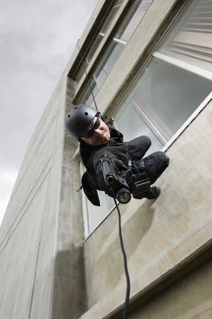 SWAT Team Officer Rappelling from Building Stock Photo - 12735683