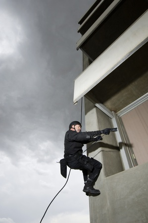 SWAT Team Officer Rappelling and Aiming Gun Stock Photo - 12737085