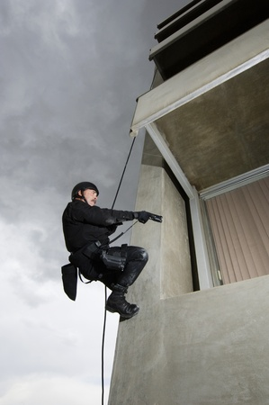 35 to 40 year olds: SWAT Team Officer Rappelling and Aiming Gun