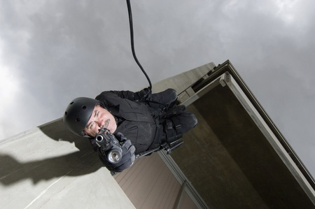 SWAT Team Officer Rappelling from Building Stock Photo - 12737087