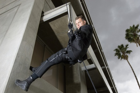 SWAT Team Officer Rappelling from Building Stock Photo - 12737088