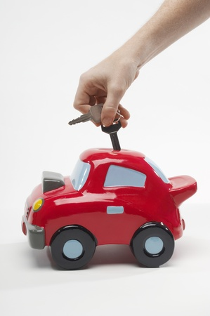 Hand Putting Car Keys in Car Shaped Piggy Bank Stock Photo - 12737186