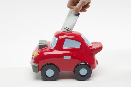 Hand Putting Money in Car Shaped Piggy Bank Stock Photo - 12737187