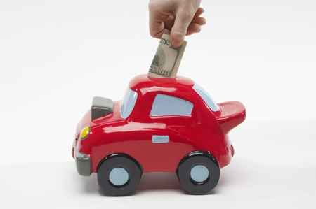 Hand Putting Money in Car Shaped Piggy Bank Stock Photo - 12737188
