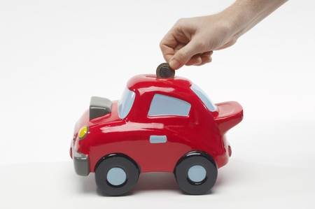 Hand Putting Money in Car Shaped Piggy Bank Stock Photo - 12737189
