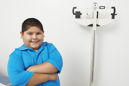 childhood obesity: Boy with arms crossed in hospitalportrait