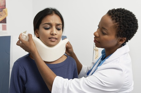 Female doctor puting brace on patient's neck Stock Photo - 12737268