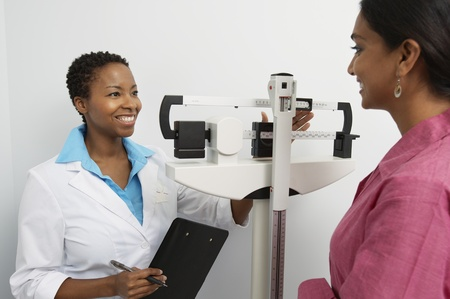 unknown age: Female doctor weighing patient