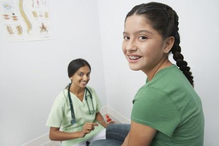 Female doctor examining girl with reflex hammer Stock Photo - 12737305