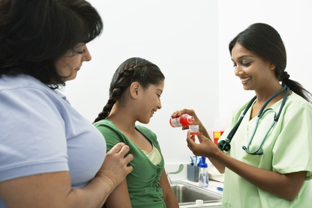 Female doctor pouring medicine for girl Stock Photo - 12737310