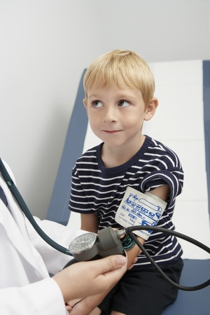 Doctor taking blood pressure of boy Stock Photo - 12737390