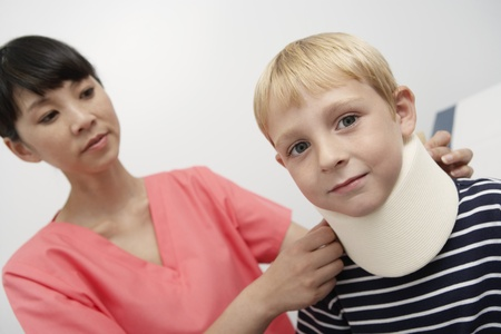 Nurse assisting boy wearing neck brace in hospital Stock Photo - 12737396