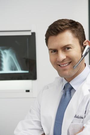 earpiece: Doctor wearing earpiece in hospitalportrait LANG_EVOIMAGES