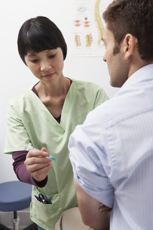 Doctor injecting male patient in hospital Stock Photo - 12737424