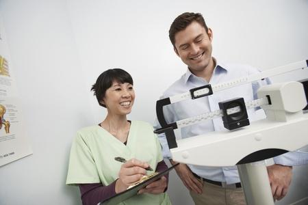 weighing scales: L'uomo in piedi sulla bilancia, accanto infermiera in ospedale