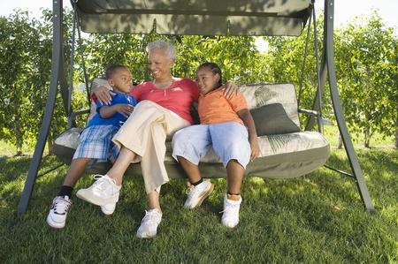 Grandmother with grandchildren on outdoor swinging chair Stock Photo - 12737536