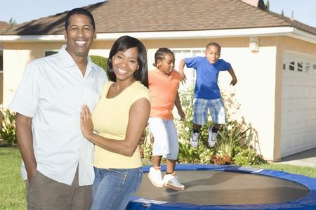 mixed age range: Family outside house children on trampoline LANG_EVOIMAGES