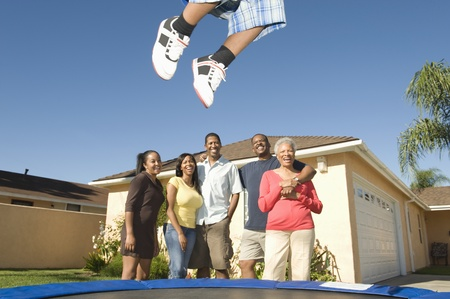 Family watching boy jumping on trampoline Stock Photo - 12737540