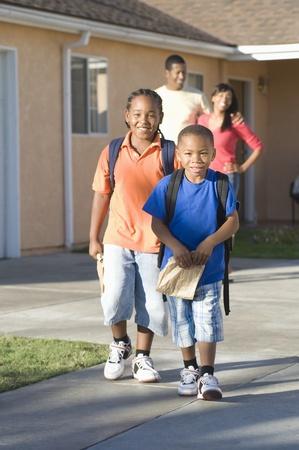 ni�os saliendo de la escuela: Los padres vigilar a los ni�os salir de la casa