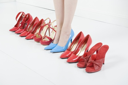 high heeled shoe: Line of red shoes with a woman standing in blue shoes