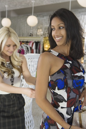 Store Assistant helps woman with dress Stock Photo - 12737553