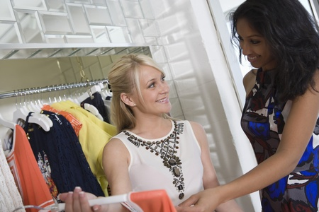 Shop assistant helps woman with dress Stock Photo - 12737555
