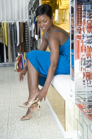 high heeled: Woman tries on gold high heeled sandals