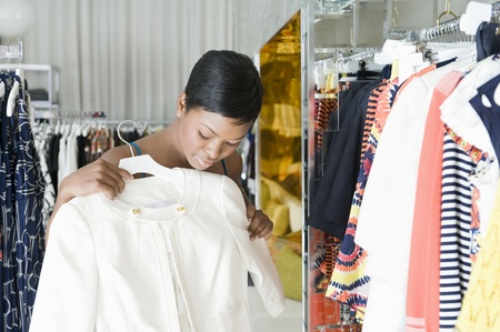 Woman considers white jacket in clothes store Stock Photo - 12737566