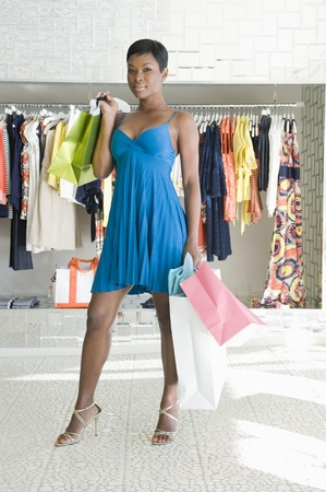 Woman stands in clothes store with shopping bags Stock Photo - 12737568