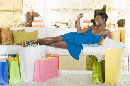 shopping spree: Woman lies with shoppig bags in store seating area LANG_EVOIMAGES