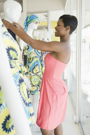 Shop assistant makes adjustment to mannequin Stock Photo - 12737578