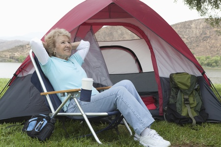 Senior woman sits relaxing outside a tent Stock Photo - 12737601