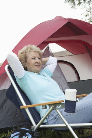 camping pitch: Senior woman sits relaxing outside a tent LANG_EVOIMAGES