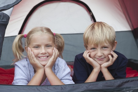 Brother and sister smiling from tent Stock Photo - 12737605