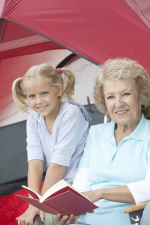 Grandmother sits reading a book with her grand-daughter outside a tent Stock Photo - 12737608