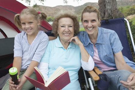 Mother daughter and grand-daughter sit reading outside tent Stock Photo - 12737609