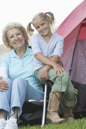 Grandmother and grand-daughter sit outside a tent Stock Photo - 12737614